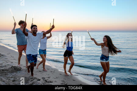 Happy smiling friends running at the beach with sparkling candles - Stock Image