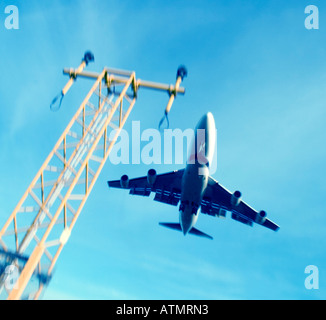 Low angle view of commercial airliner flying over approach lights. - Stock Image