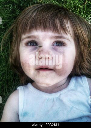 Toddler Caucasian girl laying in grass - Stock Image