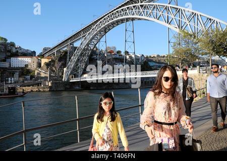 Stylish woman and child tourists walking on the Cais de Gaia in Vila Nova de Gaia side of the River Douro & view of Dom Luis bridge Porto Portugal EU - Stock Image
