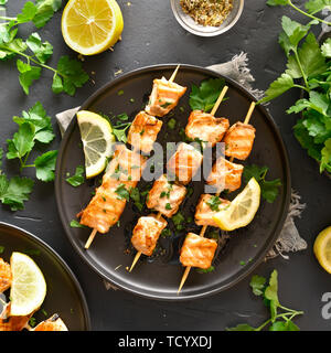 Delicious grilled salmon kebab. Barbecue salmon skewers on black stone background. Top view, flat lay - Stock Image