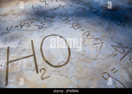 Chemical equations on a stone pavement. H2O. - Stock Image