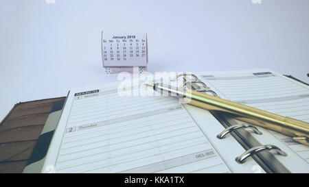 New Year calendar with journal and golden pen representing business and finance best for writers and bloggers - Stock Image