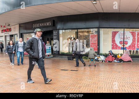 Bournemouth, UK. 23rd December 2018. Shoppers walk past a homeless person on the street in central Bournemouth. Credit: Thomas Faull/Alamy Live News - Stock Image