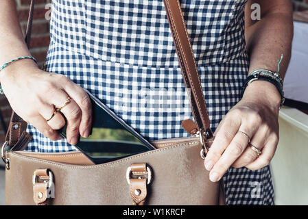 Close up of woman taking out smartphone from bag.  Business, technology, communication, leisure and people concept - Stock Image
