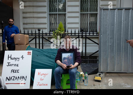 London, UK. 17th June 2019. Richard Ratcliffe on hunger strike in front of the Iranian embassy in London in protest of the detention of his wife Nazanin Zgahari in Iran over spying allegations. Embassy staff and builders bring more material on the paving, reducing Richards space. Credit: Joe Kuis / Alamy - Stock Image