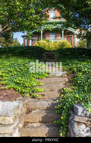 JONESBOROUGH, TN, USA-9/29/18: Rock steps lead from the sidewalk on Main Street up to a vintage home, with ivy covering the banks on both sides. - Stock Image