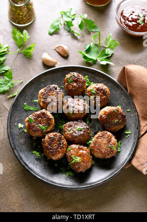 Tasty cutlets from minced meat on plate over brown background. - Stock Image