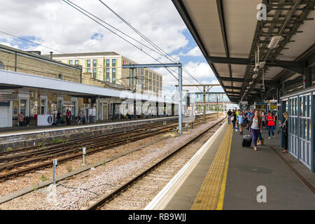 Passengers waiting on Cambridge station platforms for trains on a sunny Summer day, Cambridge, UK - Stock Image