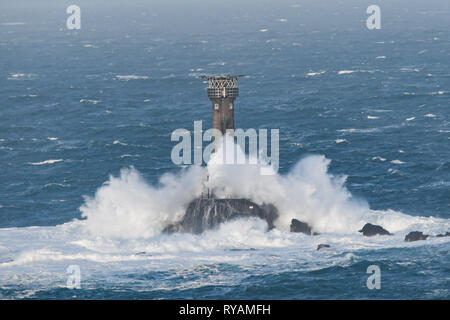 Lands End, Cornwall, UK. 13th March 2019. UK Weather. 6 crew from the French fishing vessel La Fanette were air lifted overnight after engine failure in huge seas. The local lifeboat was unable to get along, so currently the boat is drifting north west of Lands End. Seen here the huge longships lighthouse in the rough seas this morning. Credit: Simon Maycock/Alamy Live News - Stock Image