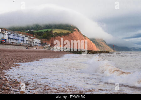 Sea front at Sidmouth, clouds rolling across cliff tops. - Stock Image