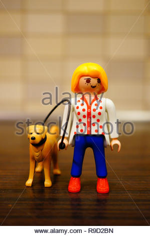 Poznan, Poland - December 22, 2018: Playmobil toy woman walking her dog out with a line in soft focus background.  - Stock Image
