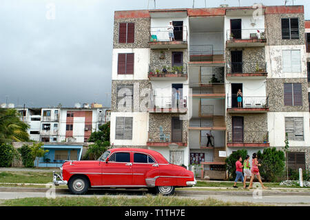 Havana, Cuba-September 09, 2018: Red vintage American car in front of very old apartment buildings. - Stock Image