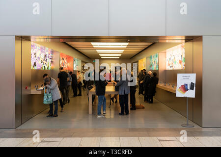 Customers browsing products in an Apple store in the Touchwood shopping centre, Solihull, UK - Stock Image