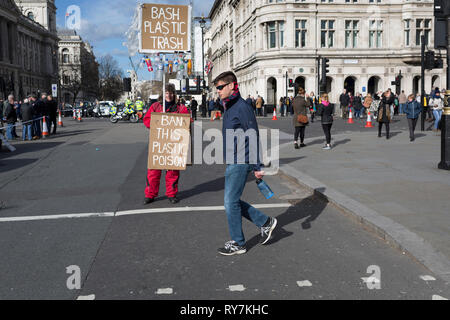 On the occasion of Commonwealth Day, a man carrying a plastic bottle walks past an environmental activist standing in Parliament Square, advocating the ban on plastics around the world, on 11th March 2019, in Westminster, London, England. - Stock Image