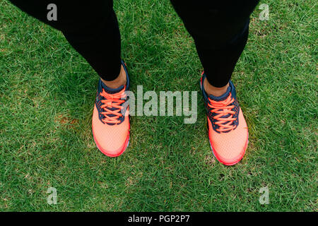 Woman feet wear bright pink sneaker shoes stand on green grass. - Stock Image