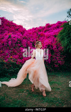 Happy bride walks among blooming trees and flowers during the honeymoon in Egypt. - Stock Image