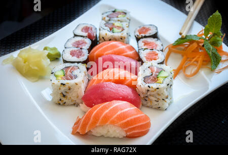 Sushi maki and California Roll with ginger and wasabi on a plate with chopsticks. - Stock Image