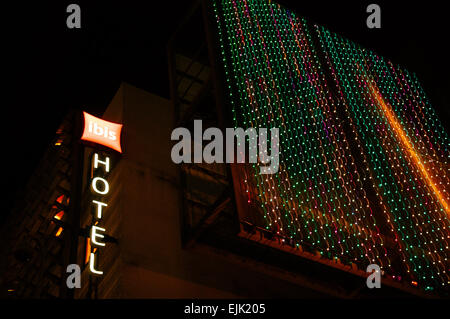 The word hotel lit up at night on the side of an IBIS hotel in Millennium Square, Bristol - Stock Image