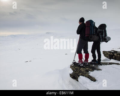 two men with heavy packs wearing snowshoes standing looking out over a  winter mountain landscape - Stock Image