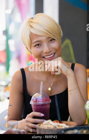 Portrait smiling, confident young woman drinking smoothie at sidewalk cafe - Stock Image