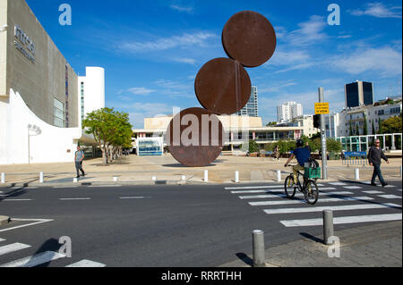 """Pedestrians and cyclists in HaBima Square, Tel Aviv, Israel. In the middle, the Hitromemut (""""elevation"""") installation by artist Menashe Kadishman, - Stock Image"""