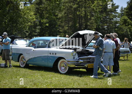 Westbury, New York, USA. June 12, 2016. Visitors are examining engine under the open hood of turquois and white - Stock Image