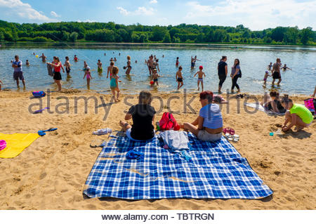 Many adults and children standing and sitting on - Stock Image