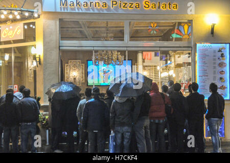 People watch a football game on a restaurant's big screen as they stand outside on the rain on Istiklal street - Stock Image