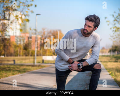 One handsome man in city park, leaning on knee - Stock Image