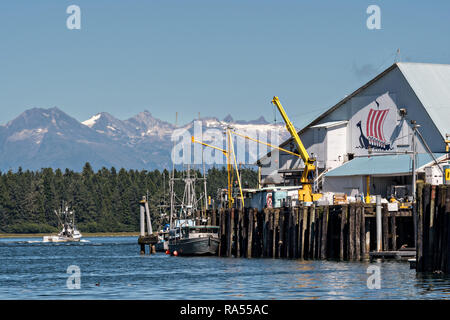 A fishing boat pulls out from the Icicle Seafoods fish docks in the tiny village of Petersburg on Mitkof Island along the Wrangell Narrows in Frederick Sound with the Alaska Coast Range of mountains behind on Mitkof Island, Alaska. Petersburg settled by Norwegian immigrant Peter Buschmann is known as Little Norway due to the high percentage of people of Scandinavian origin. - Stock Image