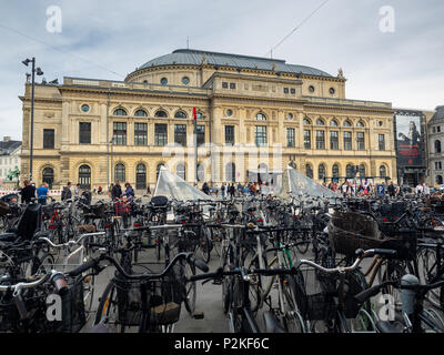Bicycle stands and pedestrians walking near the Royal Danish Theatre in Copenhagen, Denmark. - Stock Image