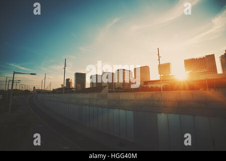 Wide angle shot of dramatic sunset with flare and godrays near highway in Barcelona with distant residential houses, - Stock Image