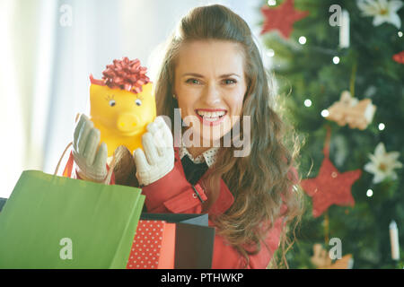 smiling young woman in red trench coat with shopping bags showing yellow piggy bank near Christmas tree - Stock Image