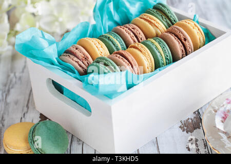Assortment of fresh french macarons packaged in a pretty white wooden box with blue tissue on a white rustic table.. - Stock Image
