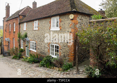 Old flint stone cottage on narrow steep street on a hill. Arundel, West Sussex, England, UK, Britain - Stock Image