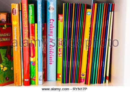 Poznan, Poland - November 18, 2018: Row of colorful Polish child books on a shelf. - Stock Image