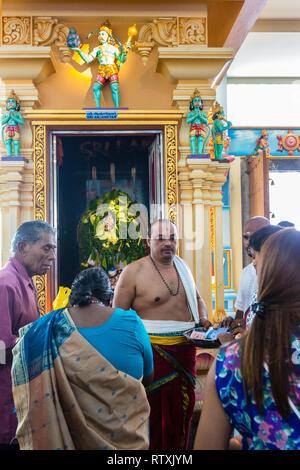 Hindu Priest Receiving Donations in front of Sri Anjaneyar Shrine, Kuil Sri Krishna Hindu Temple, Kuala Lumpur, Malaysia. - Stock Image