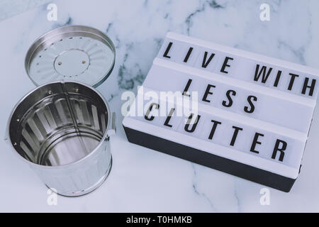 ecology and consumerism concept: live with less clutter message on lightbox with open empty trash bin - Stock Image