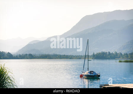 Beautiful landscape with yacht on the lake in mountains at summer morning - Stock Image