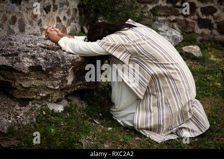 Jesus in agony praying in the garden of olives before his crucifixion - Stock Image