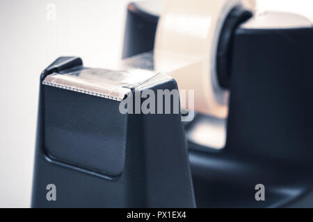Macro Of A Black Sellotape Holder On A White Office Desk - Stock Image