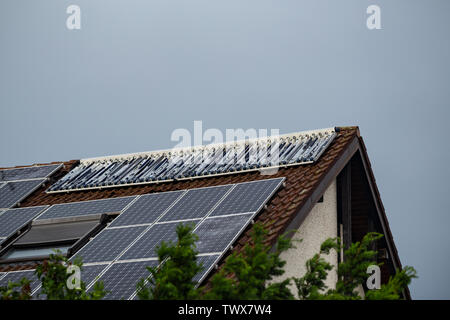 Hail damage to solar collectors on the roof of a house after a thunderstorm - Stock Image