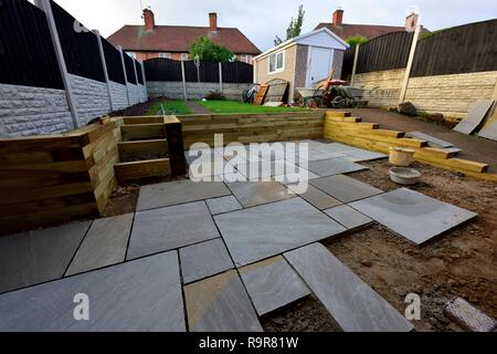 Indian paving slabs being laid on a garden patio garden renovation UK - Stock Image