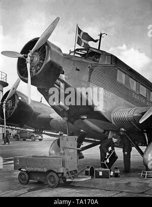 A Junkers Ju 52 of the Danish airline DAL at Berlin-Rangsdorf Airport. Luggage is loaded into the cargo hold. - Stock Image
