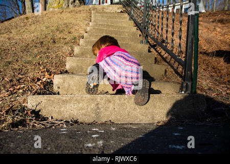 An infant girl crawls up a flight of stone stairs on a sunny day. - Stock Image