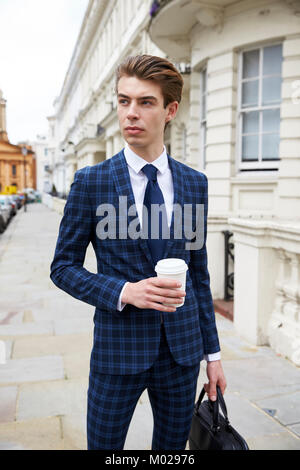 Young man in blue check suit standing in street with coffee - Stock Image