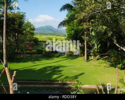 View from Hotel extensive grounds across rice fields to distant Luang Prabang mountain range Laos Asia - Stock Image