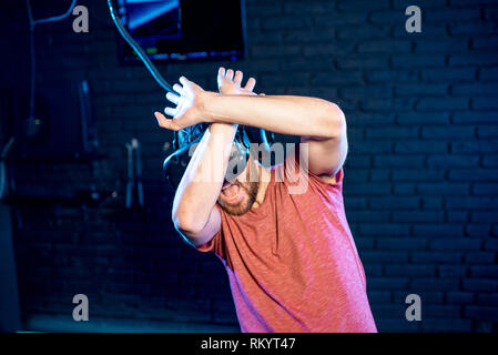 Scared man playing game in virtual reality using VR headset in the playing room - Stock Image