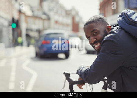Smiling young businessman commuting, riding bicycle on sunny urban street - Stock Image